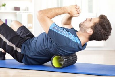 man lying on a foam roller while doing an exercise royalty free image 509421384 1545148853